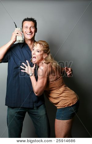 a woman is happy that her husband or boyfriend is talking on his 1980s era cellular telephone isolated on grey