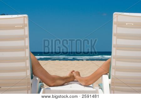 Couple In Beach Chairs Holding Hands Near Ocean