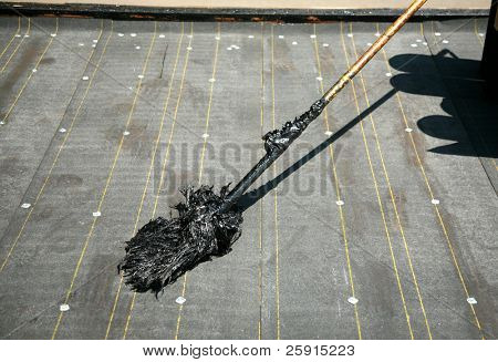 tar mop on a new roof ready to be used to lay down hot molten tar