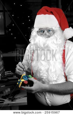 Santa Claus paints a toy as he makes Christmas Presents for children around the world, black and white and colorized for a Retro Look