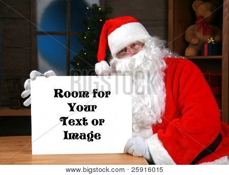 """""""santa claus"""" holds a blank white sign with """"room for your text or image""""  while in his workshop in the """"north pole"""""""