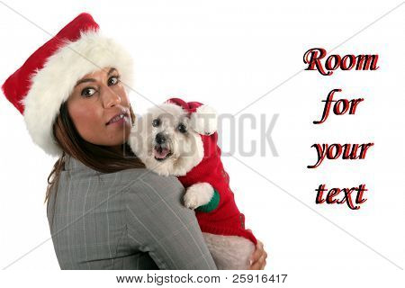 "a beautiful young woman in a santa hat holds her ""bichon frise"" who is wearing a christmas outfit, isolated on white, with room for your text"