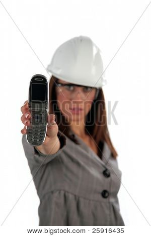 beautiful young woman in contractor hard hat with her cell phone, isolated on white