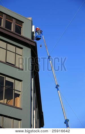 """eine nicht identifizierbare Mann in einem """"Mann Aufzug"""" oder Crain arbeiten auf einem Gebäude-Schild"""