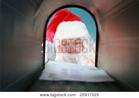 Papá Noel recibe su correo de su buzón, visto desde adentro hacia afuera