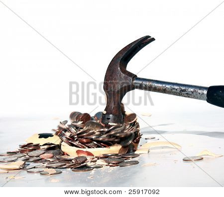 a hammer breaks a piggy bank with money and parts flying all over
