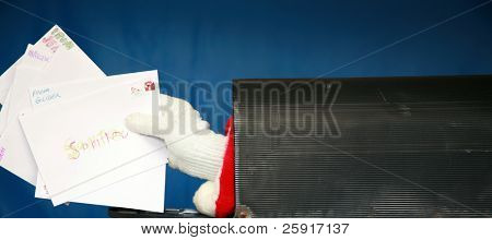 a Santa Claus hand reaches out and holds a  letter from inside a mail box