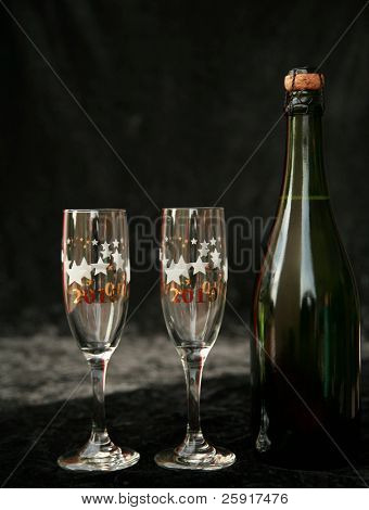 2010 champagne glasses and  bottle with its cork, on black velvet