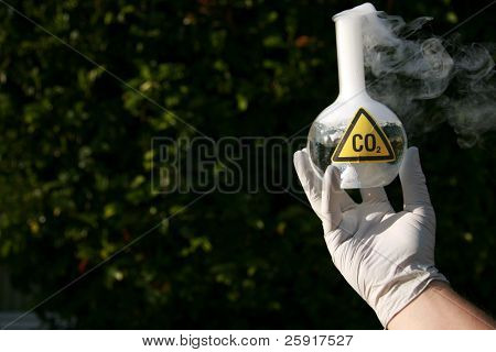 a Scientist holds a 500ml beaker filled with CO2 representing carbon dioxide emmissions and the cause of