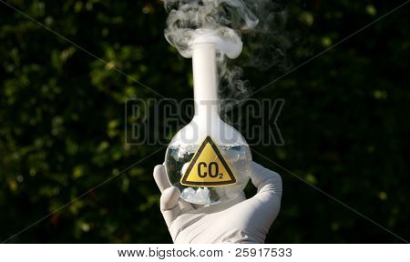 """a Scientist holds a 500ml beaker filled with CO2 representing carbon dioxide emmissions and the cause of """"Global Warming"""""""