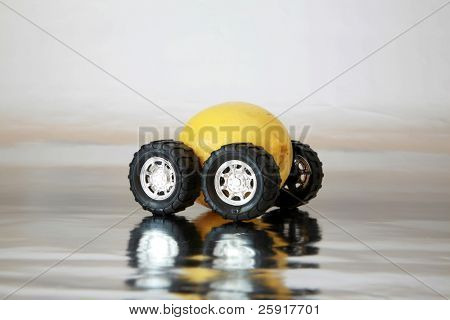 "generic truck wheels on a yellow lemon represents the catch phrase ""this car is a Lemon"" on silver"