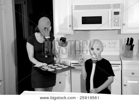 a mother and son enjoy hot fresh baked cookies in their kitchen while wearing gas masks in a post nuclear future in black and white for a edgy futuristic image