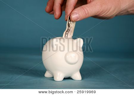 a person taking or adding money to a piggy bank