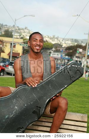 a young man poses with his old worn out guitar case outside in a park