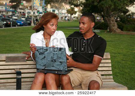 ein Afroamerikaner Mädchen an ihrem Freund mit was sie findet, während mit einem Laptop verärgert ist com