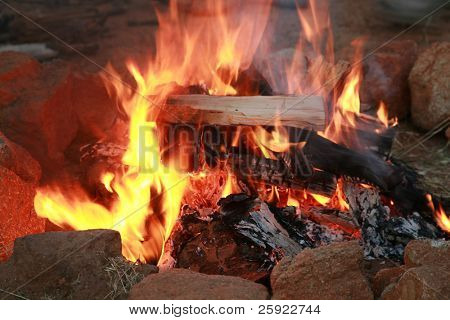 a camp fire in a fire pit at a campsite