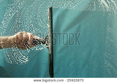 un squeegiee de lavadora de ventana limpia una ventana mientras lavado de ventana