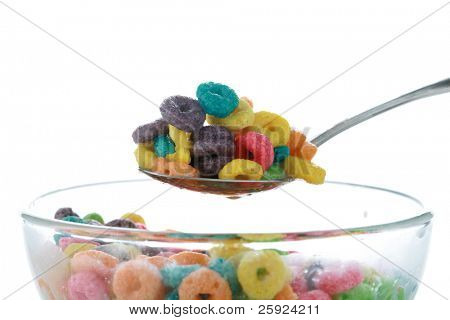 kids breakfast cereal loops with a spoon in fresh cows milk or could be almond milk or even soy milk. isolated on white