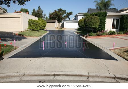 fresh hot tar aka black top on an ashphalt driveway in a neighborhood