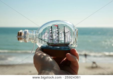 a ship in a bottle held in a persons hand with the beautiful blue pacific ocean as a background