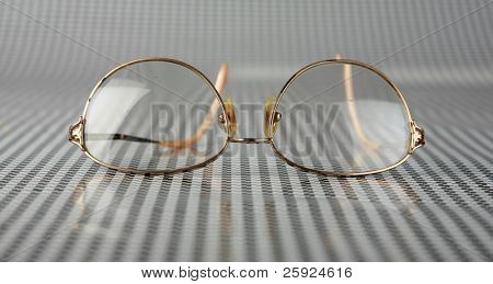old gold framed prescription reading glasses lay upon a black and white background waiting for the owner to find them so they can see again