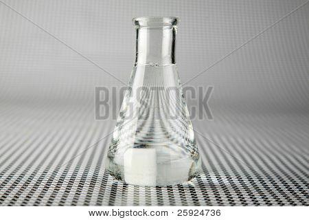 un químico o científico de investigación médica agrega productos químicos a un matraz erlenmeyer de un químico violento