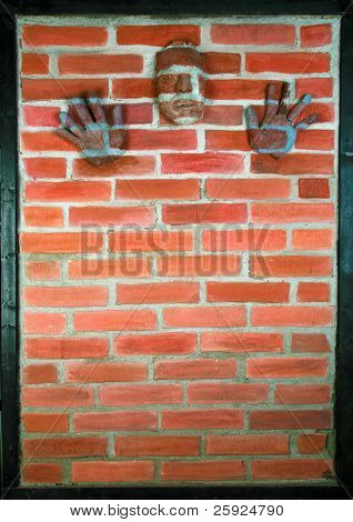 "my origional 3-D sculpture artwork, titled ""Urban Camouflage"" my face and hands (made out of paper mache') on a z-brick wall"