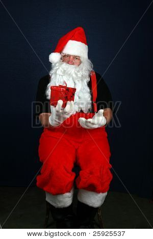 Santa Claus holds a christmas present he is going to give to some lucky boy or girl for Christmas as he sits in a chair
