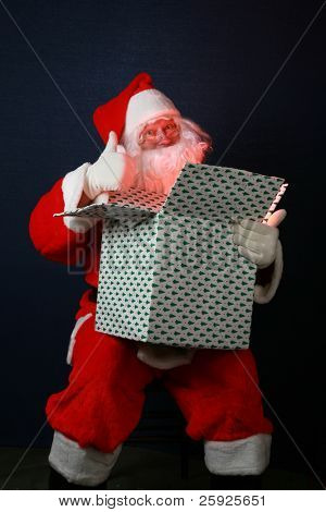 Santa Claus holds a Christmas Present filled with Christmas Magic