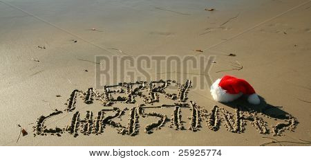 "The words ""Merry Christmas"" written in the wet sand on a Southern California Beach with a ""Santa Hat"" and the ""Pacific Ocean"" in the background"