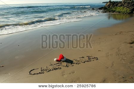 """the word """"California"""" written in the wet sand on a southern california beach with a """"Santa Hat""""  and a blue sky and nice tide and waves from the pacific ocean"""
