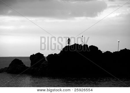 "silouette of a ""Cliff Diver"" as he prepares to jump off a cliff into the ocean"