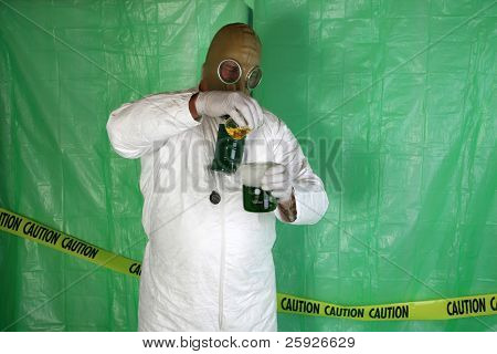"""A Nuclear Scientist or Chemical Engineer wears a white Hazmat Suit, Gas Mask, and Gloves as he mixes dangerous chemicals together while in a temperary plastic wrapped """"Safety Zone"""" in a Disaster area"""