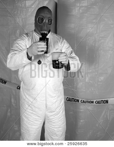 "A Nuclear Scientist or Chemical Engineer wears a white Hazmat Suit, Gas Mask, and Gloves as he mixes dangerous chemicals together while in a temperary plastic wrapped ""Safety Zone"" in a Disaster area"