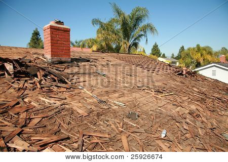 the roof of a house being torn off and being prepaired to be re-roofed with new shingles