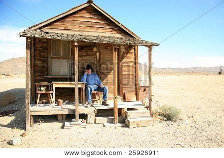 an old cowboy sits on the porch of his home after a hard day of gamblin' n drinkin' n chasin' saloon girls round the piano