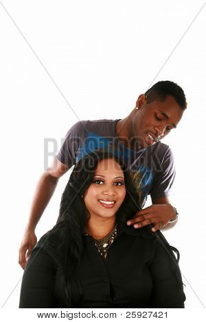 a beautiful african american woman has her hair attended to by her favorite hair stylist for a photo shoot in a studio. isolated on white with room for your text. focus on the woman