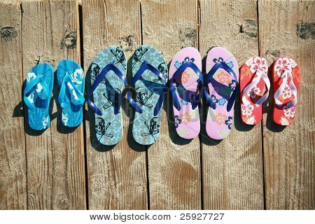 Colored flip-flops of a family of four by the beach at the ocean