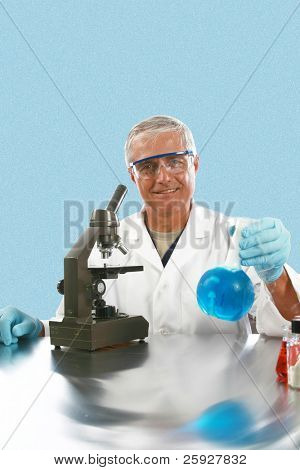 a scientist or chemist smiles as he works in his laboratory with a blue background