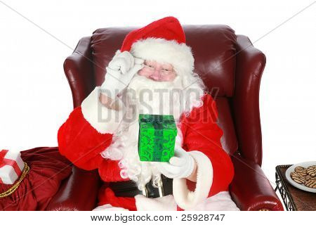 Santa Claus holds a green christmas present to you the viewer. isolated on white with room for your text. Focus is on the green christmas present with santa slightly out of focus