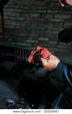Detail of a car mechanic working on a car at the car repair shop, car in background