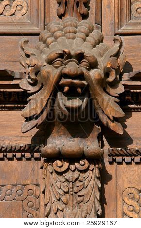 Medieval wooden sculpture of a fabulous monster on the gate of the Old Town Hall in Prague, Czech Republic