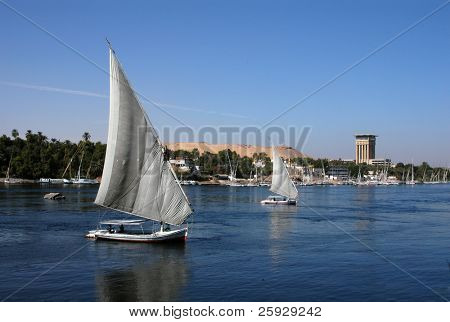 Two feluccas, traditional Egyptian sailing vessels, on the River Nile in Aswan, Egypt