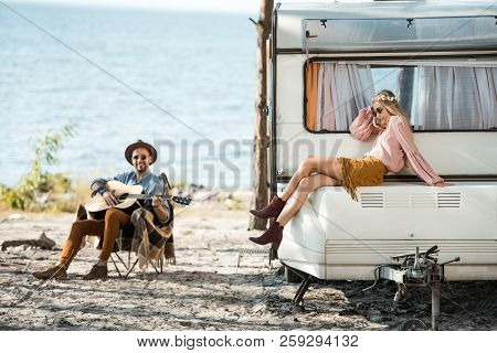 Hippie Girl Sitting On Campervan