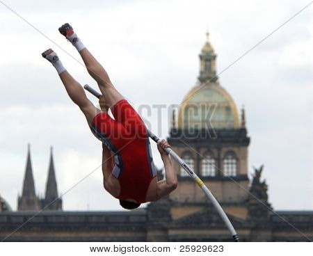Athlete clearing the bar during a pole vault event in Prague, Czech Republic