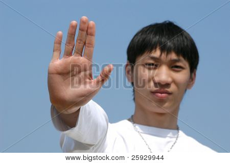 Young Asian man holding hand up saying 'Stop' or 'No' - palm in focus