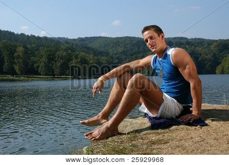 Muscular male model with army tags sitting at the beach