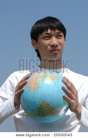 Young Asian man holding a terrestrial globe