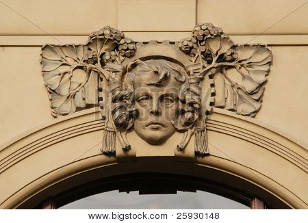 Allegory of industry, a stucco mask on the facade of the Municipal House in Prague, Czech Republic