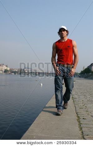 Young sexy man walking along the embankment in Prague, Czech Republic.